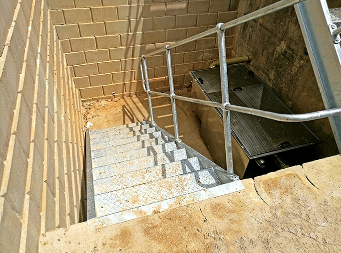 kitchen grease trap storage area with stairs and retaining wall