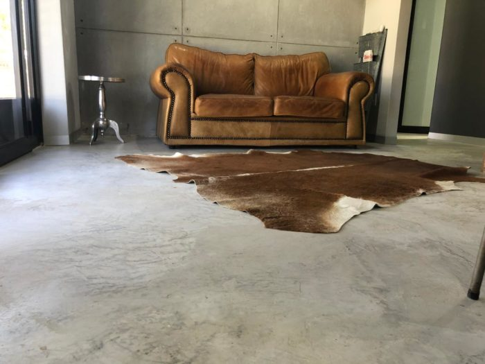 cement floor with leather couch and animal skin rug