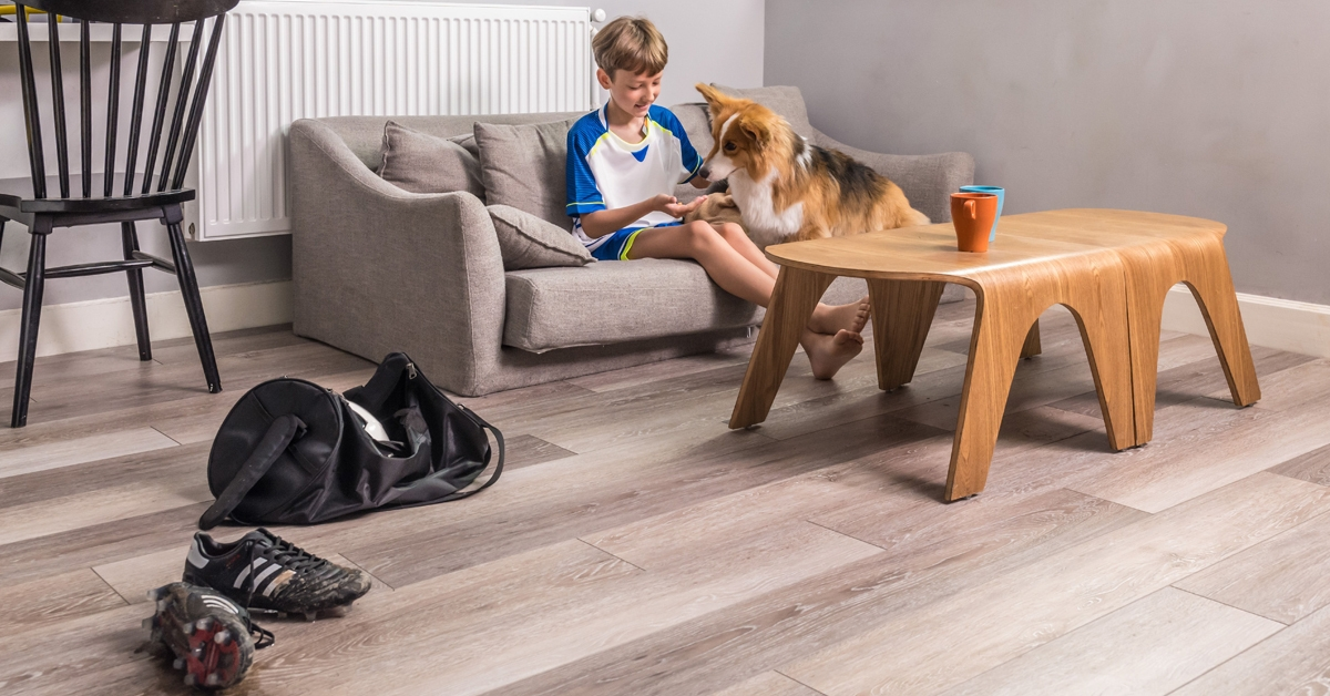 astroguard flooring designed for pets and home stains. A boy sitting on the couch with his dog. Soccer tog bag and spike shoes on the luxury vinyl tile flooring.